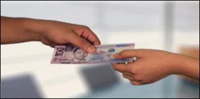 A New Philippine Peso Bill handed to someone